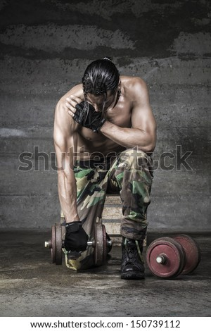 portrait of muscle athlete with camouflage pants weightlifting on wall background - stock photo