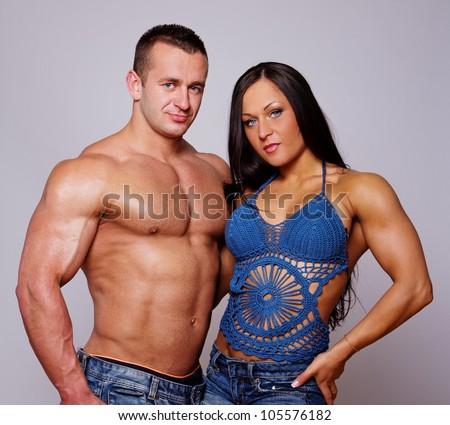 Portrait of muscle couple posing in studio - stock photo