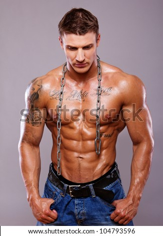 Portrait of muscle man posing in studio with chain - stock photo