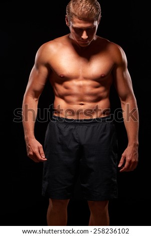Portrait of muscular heavy sexy man with naked torso, dressed in black shorts, looking down with shadow on the face. Isolated on black background - stock photo