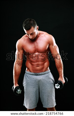 Portrait of muscular man holding dumbbells on black background
