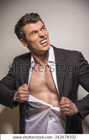 Portrait of muscular man is ripping his shirt isolated over white background. - stock photo