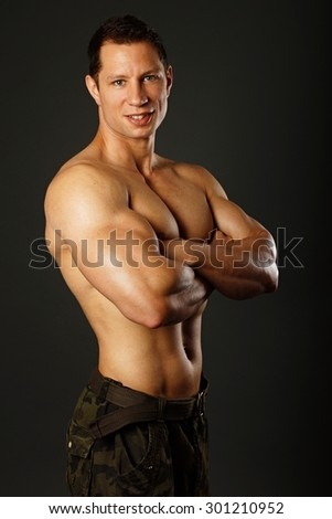 Portrait of muscular smiling muscular man on gray background