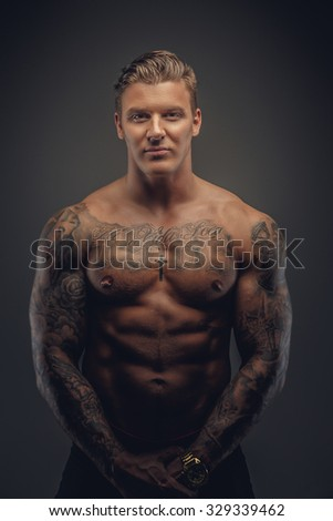 Portrait of muscular tattooed man in shadows isolated on grey background.