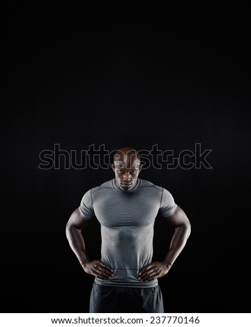 Portrait of muscular young man in sportswear staring at camera against black background. African athlete with his hands on hips posing confidently. - stock photo