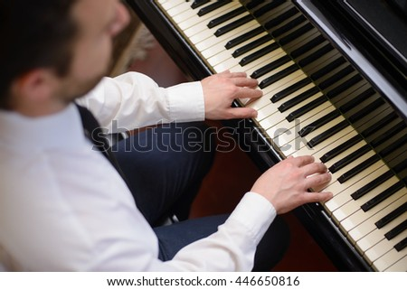 Portrait of music performer playing his piano - stock photo