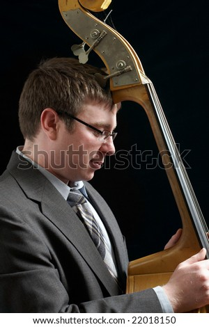 Portrait of musician leaning against upright bass - stock photo