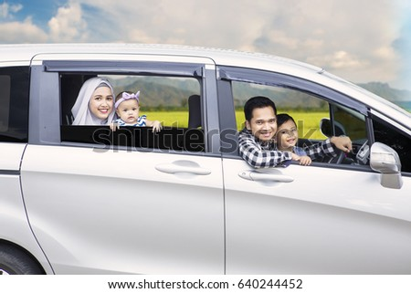 Portrait of Muslim family looking out of a car window while driving for travel on vacation