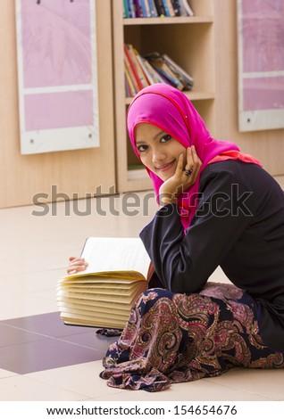 Portrait of muslim girl reading book  - stock photo