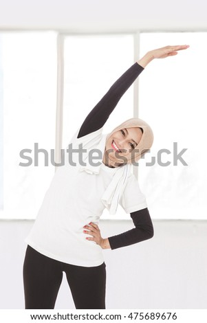 portrait of muslim sporty woman doing body and hand stretching