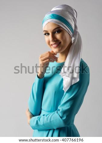 Portrait of muslim woman on grey - stock photo