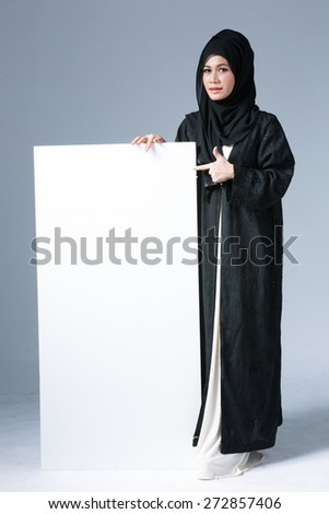 portrait of muslim woman wearing scarf showing blank board - stock photo