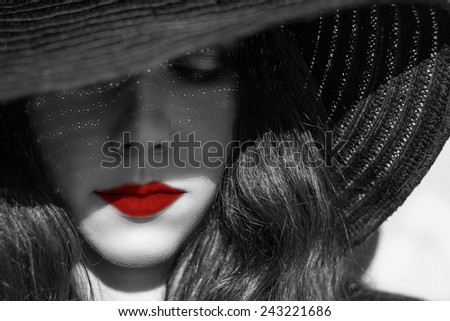 Portrait of mysterious beautiful young woman  in  black raffia hat. Trendy glamorous sexy fashion smoky eyes makeup. Sensual lips. Black and white image. Art photo. Red lips. Model shooting.