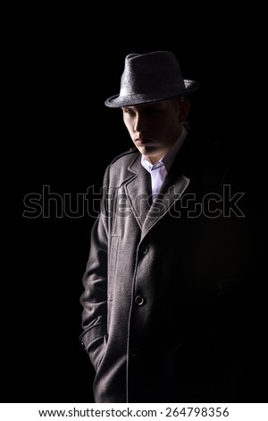 Portrait of mysterious Caucasian man in black hat and coat with tough expression walking in darkness, low key studio shot against black background - stock photo