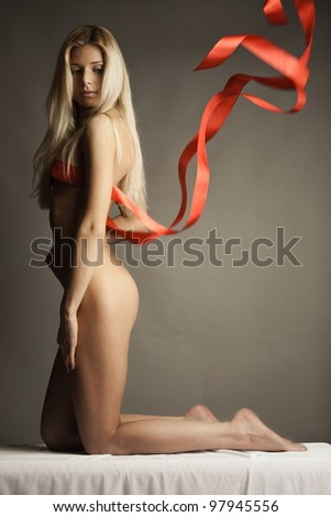 Portrait of naked woman wearing red ribbon as lingerie - stock photo