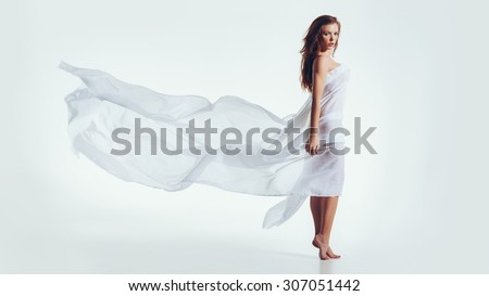 Portrait of naked woman wrapped in white fabric looking at camera with an attitude. Sensuous caucasian female model posing over white background. - stock photo