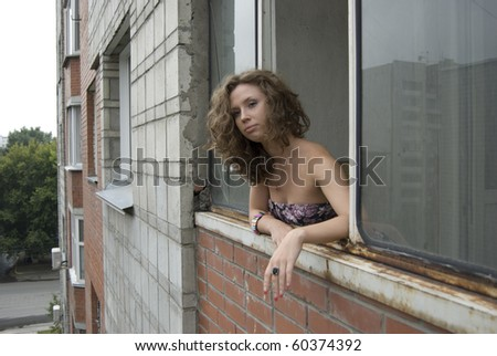Portrait of nasty woman looking from her balcony