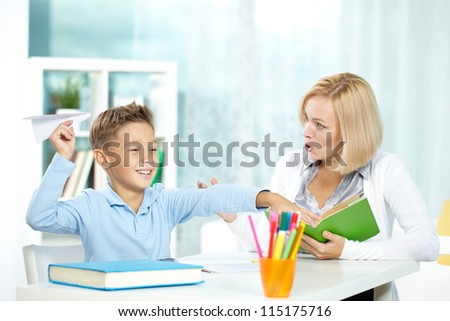 Portrait of naughty boy playing with paper plane at workplace and his indignant tutor looking at him - stock photo
