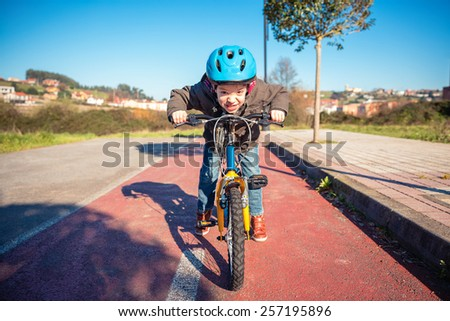 Portrait of naughty boy with defiant gesture over his bike ready to run on a cycleway - stock photo