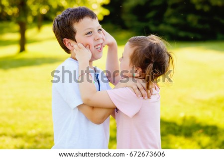 Portrait of naughty little girl pinching cheeks of her brother outdoor. Little boy embracing her and laughing
