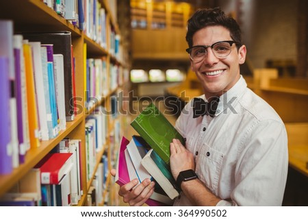 Portrait of nerd holding books in library