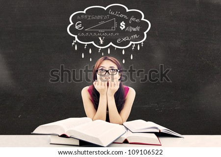 Portrait of nervous female college student with textbooks biting her nails looked thinking about her exams - stock photo