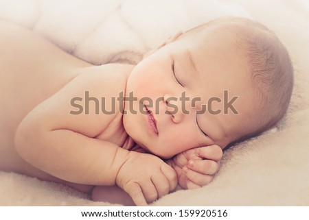 Portrait of newborn baby boy sleeping on soft beige cover - stock photo