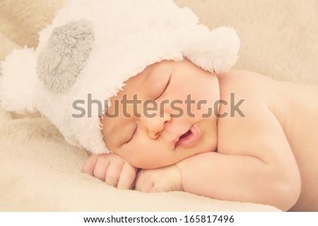 Portrait of  newborn baby boy wearing funny bear shape hat sleeping on soft beige cover - stock photo