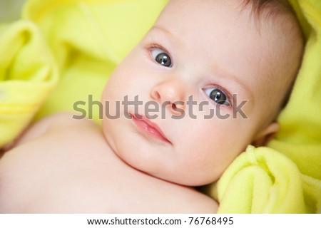 Portrait of newborn baby on yellow towel - stock photo