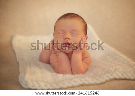 Portrait of Newborn Baby Sleeping on Hands on floor - stock photo