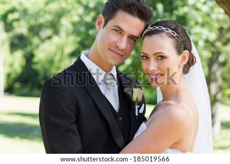 Portrait of newly wed couple smiling together in garden - stock photo