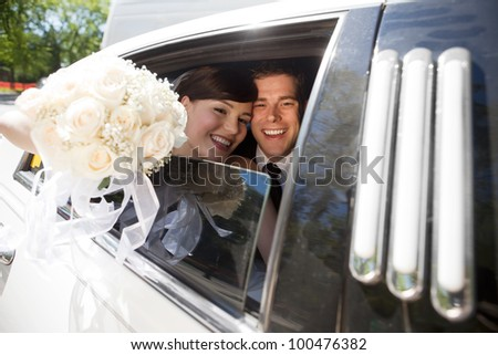 Portrait Of Newlywed Couple Smiling Sitting In Limousine Holding Bouquet In Hand. - stock photo