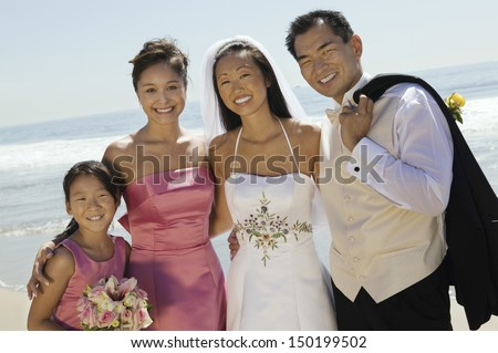 Portrait of newlywed couple with flower bouquet and bridesmaid on beach - stock photo