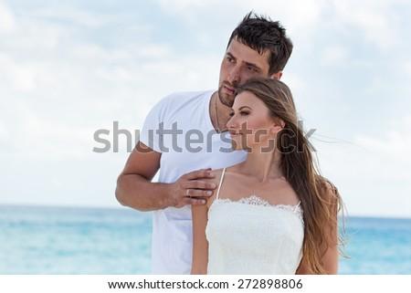 Portrait of newlyweds hugging on seashore and enjoy a romantic moment - stock photo