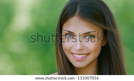 Portrait of nice dark-haired young woman, against background of summer green park. - stock photo