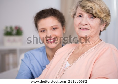 Portrait of nice elderly woman and young caregiver - stock photo