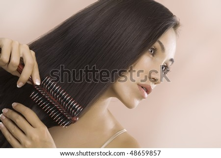 Portrait of nice young woman getting busy with her hair