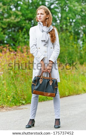 Portrait of nice young woman with handbag, against background of autumn park.