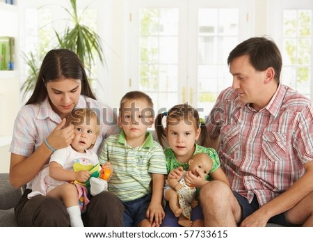 Portrait of nuclear family with 3 children sitting on sofa at home.? - stock photo