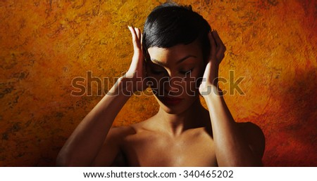 Portrait of nude female model holding her head - stock photo