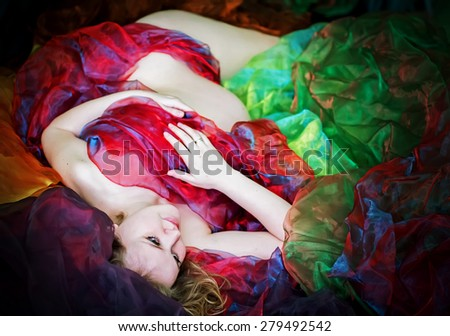 Portrait of nude pregnant young woman muffled in open-work colorful fabric. Horizontal image with selective focus - stock photo