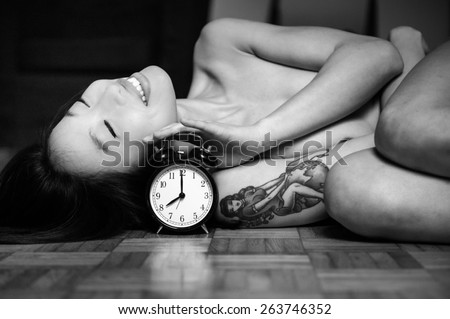 Portrait of nude young asian woman lying and smiling on wooden floor with alarm clock in black and white - stock photo