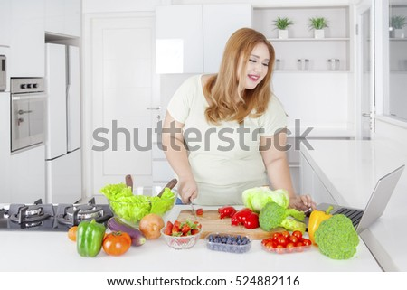 Portrait of obese woman cutting paprika by using knife while looking receipt at laptop