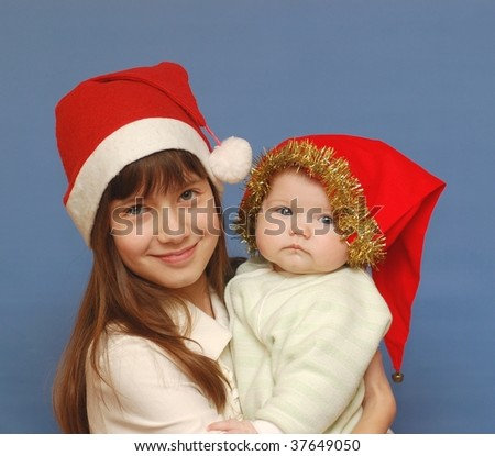 Portrait of of beautiful teenage girl and baby in red hat - stock photo
