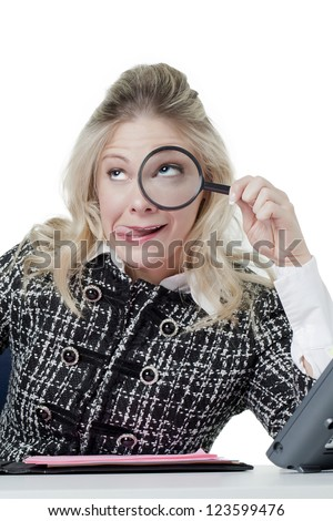 Portrait of office girl making funny face while holding magnifying glass against white background - stock photo