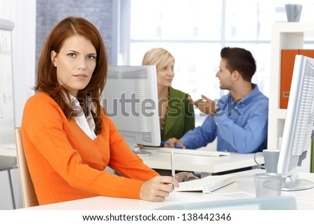 Portrait of office worker woman sitting at desk, looking at camera, colleagues at background.