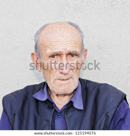 Portrait of old hoary man in blue shirt - stock photo