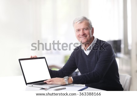 Portrait of old professional man sitting at office in front of blank screen laptop and looking at camera. - stock photo