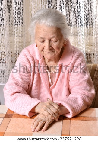 Portrait of old sad woman - stock photo