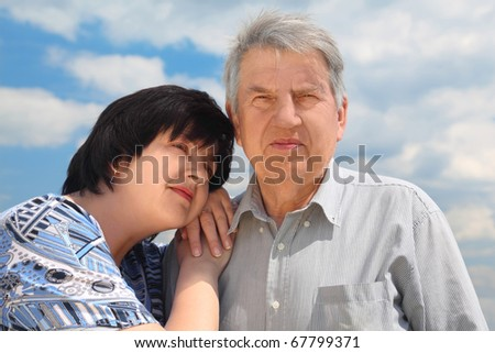 portrait of old senior, his adult daughter leaning to his shoulder, sky with clouds - stock photo